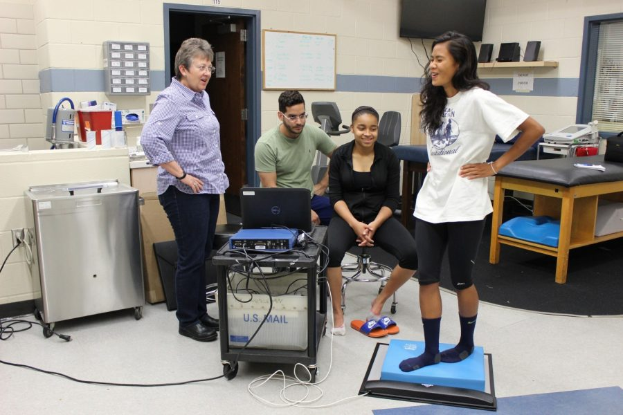 Dr. Pam Rast (left) shows exercise science majors how to use Balance Error System to measeure concussions.