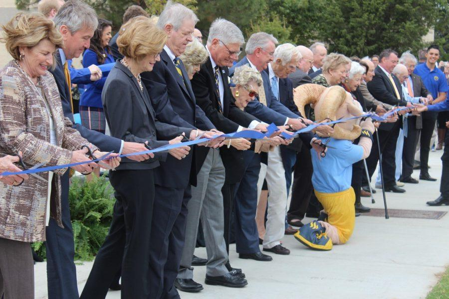 Photo by Valerie Spears Alumni, Board of Trustees and various others prepare to cut the ceremonial ribbon.