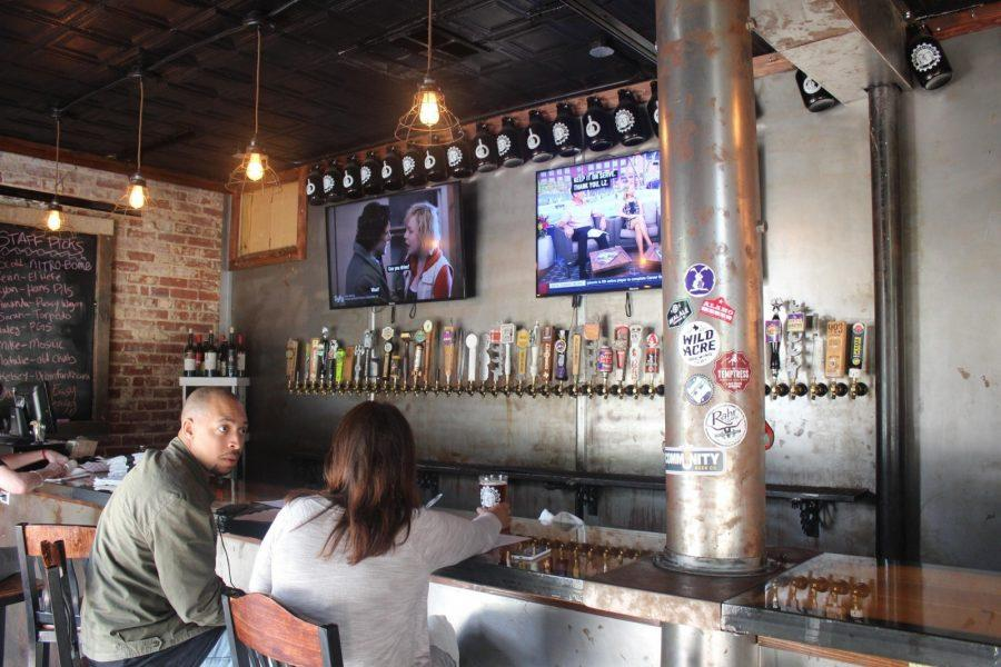 Patrons+sit+at+the+bar+and+enjoy+one+of+the+53+craft+beers+on+draft+at+Pouring+Glory+Growler+Filler+Station%2C+located+just+five+minutes+from+campus.+%28Photo+by+Cheyan+Fite%29