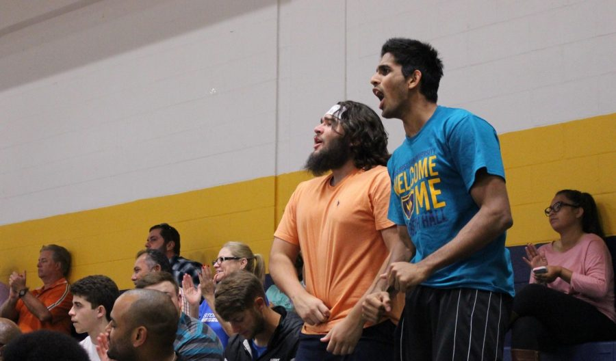 Zack Lanham (left), who is a cheerleader and football player, and basketball player Praneeth Udumalagala cheer on the Lady Rams volleyball team at a recent game.