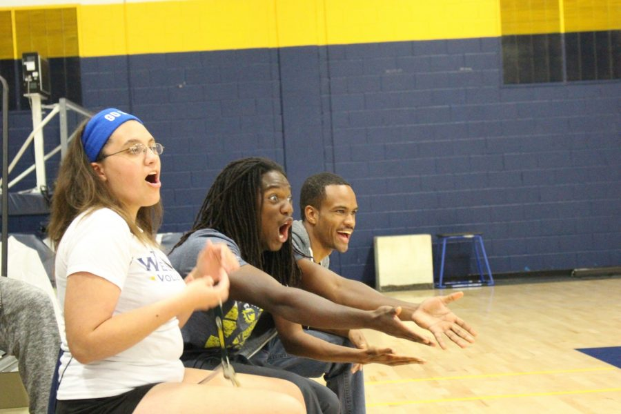 Ram Squad members Katie Matthews, Anthony Harper II and Akeel Johnson cheer at a Friday night volleyball game against John Brown University.