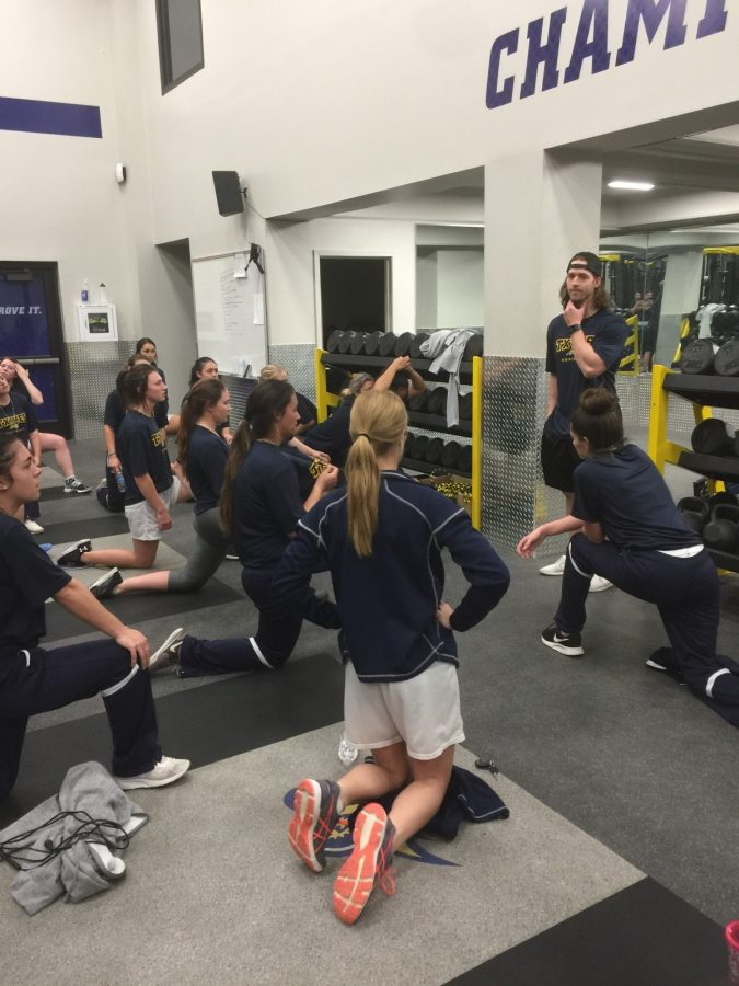 Parker+Purvis+speaks+to+softball+players+about+their+strength+and+conditioning+workout+in+the+weight+room.+Photo+taken+by+Sam+Bastien.