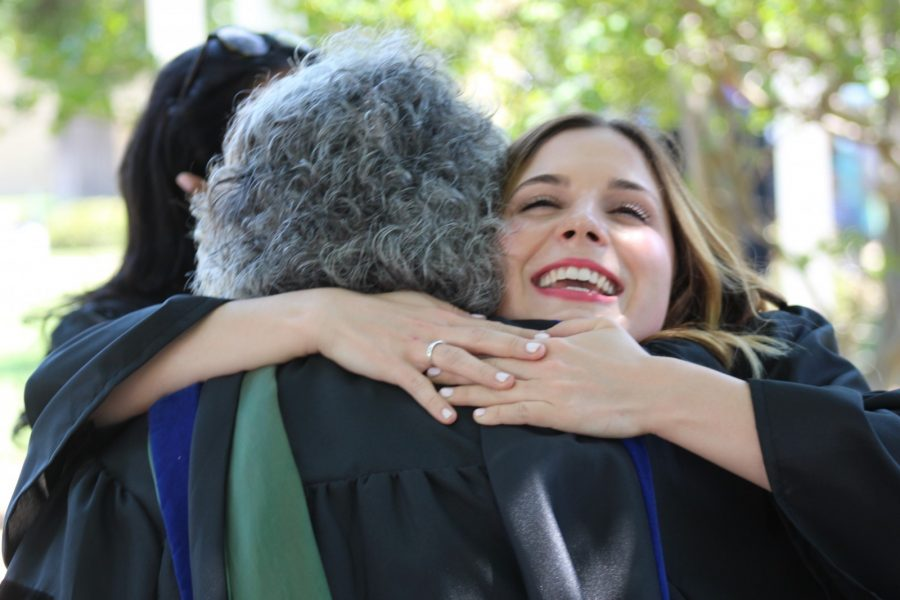 Senior mass communication Sarah Owens hugs Associate Professor of Mass Communication Dr. Kay Colley after robing. Photo by Hannah Onder