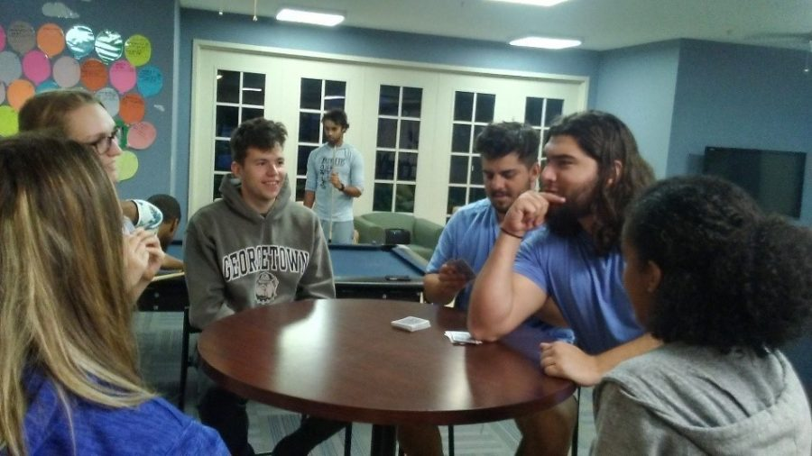 Resident assistants Alanna James and Zach Lanham play cards with residents at the welcome back party. Photo by Kaylee Conrad