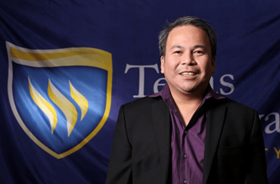 Dr.Tito Tubog poses for staff photos in front of the Texas Wesleyan flag. Photo from txwes.edu.