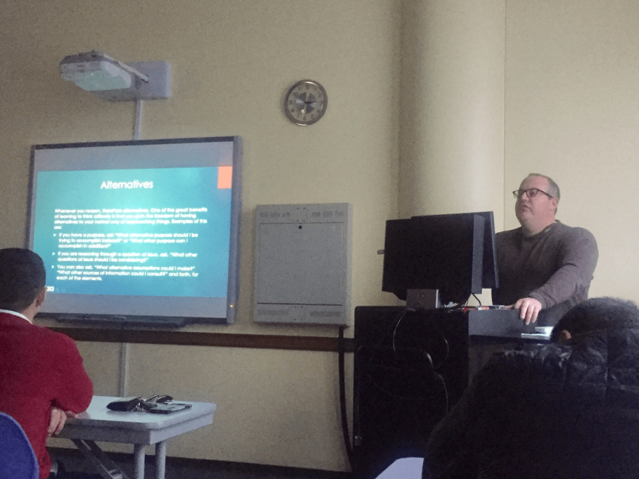 Dr. Wade Thompson discusses his critical-thinking PowerPoint with students. Photo by Massaran Kromah