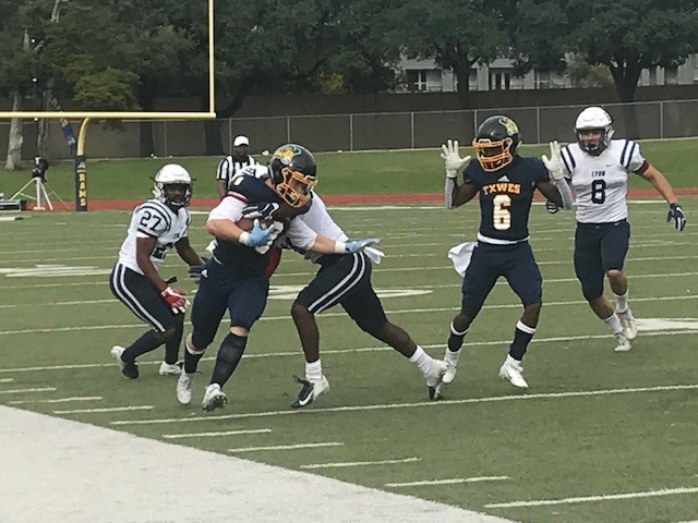Wide receiver LeMant Monroe helps wide receiver Cole Maxwell as he runs with the ball. Photo by Ashton Willis