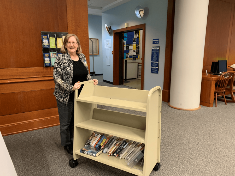 Risa Brown poses for a picture while carrying a shelf of books to their correct destination.