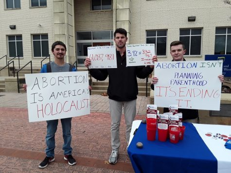 Young Conservatives of Texas members Matthew Breedlove, Trace Lutteringer and Nicholas Davis protest outside the West Library. Photo by Elizabeth Lloyd