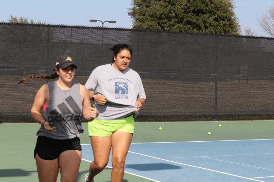 Maggie Brasher (left) and Emily Rodriguez warm up before practice. Photo by LaTerra Wair