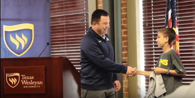 Jaiden Mehta shakes head baseball coach Robert Garzas hand at a signing event on March 25.