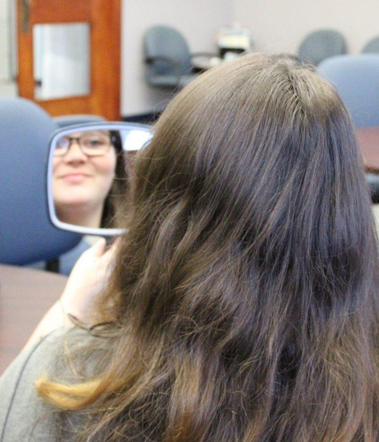 """Senior business major Joyce Pedigo poses with a mirror to symbolize her morning routine of waking up, looking into a mirror and giving herself a compliment. """"You can't really do anything full-heartedly if you can't completely care for yourself.""""  Photo by Hannah Onder"""