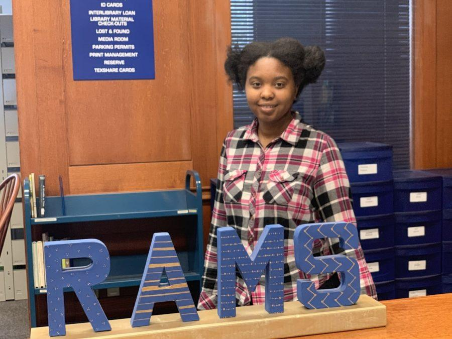 Kiana Veasley poses for a photo at her job at the Eunice and James L. West library. Photo by Massaran Kromah
