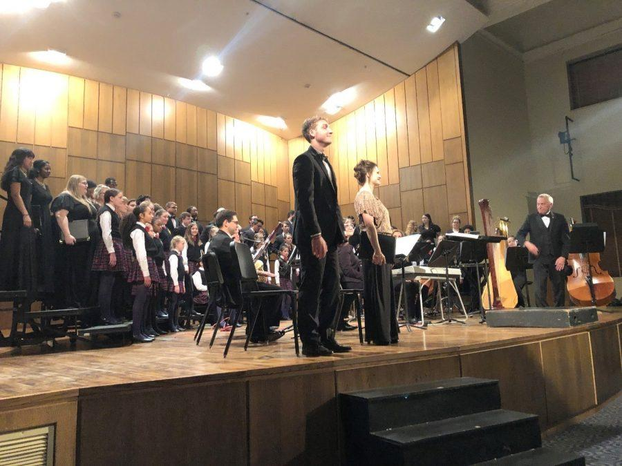 Dr. Jerome M. Biershenck introduces his choir and orchestra after a performance. Solo artists Allen Michael Setford and Allison Whetsel Ward (left to right at left of photo) stand for recognition. Photo by Mallory Marks