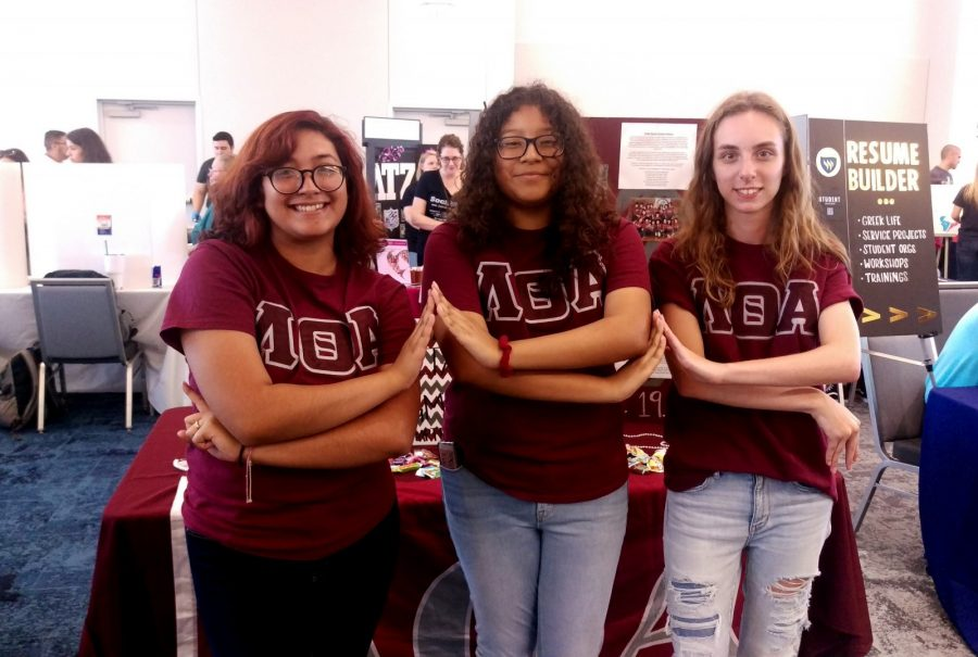 Lambeda Theta Alpha Latin Sorority members Angela Castillo, Elizabeth Gomez, and Devyn Teague (left to right) pose in front of their booth as they work to recruit new sisters at the Presidents Picnic. Photo by Hannah Onder