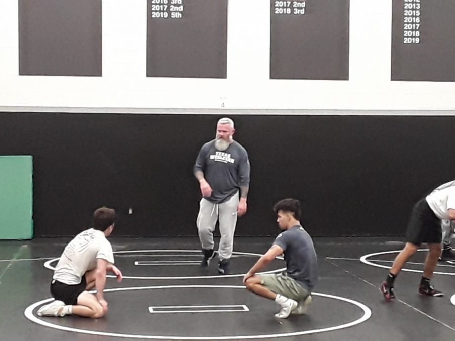 Head wrestling coach Ray Bedford (center) and assistant coach Ronnie Bresser (right) engage with a wrestler during practice at Carroll High School. Photo by Elizabeth Lloyd