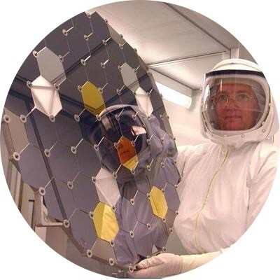 Dr. Eileen K. Stansbery in the Genesis Curator Clean Room dressed in a Dryden HEPA Filter suit holding a collector plate. The collector plate is an ultra-pure array composed of different materials used to extract solar wind atoms.  Photo is courtesy of NASA Johnson Space Center.
