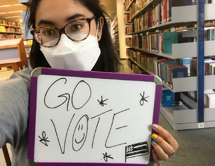 """Manuela Lee holds up a """"Go Vote"""" sign. Lee hopes students will research candidates and learn their stances on various policies. Photo courtesy of Manuela Lee."""