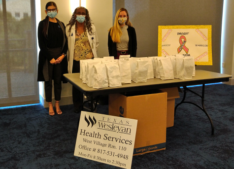 Left to right: Chelsea Sepolio, Anice Lewis-Hollins and Jesse Pyle pose at the goodie bag table at the flu shot event.